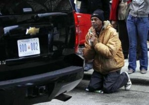An unidentified man drops to his knees that the passing of the presidential motorcade.