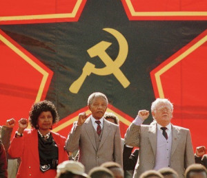 Winnie Madikizela–Mandela, Nelson Mandela and CPSA Chairman Joe Slovo give the clenched fist salute in front of the Hammer and Sickle logo.