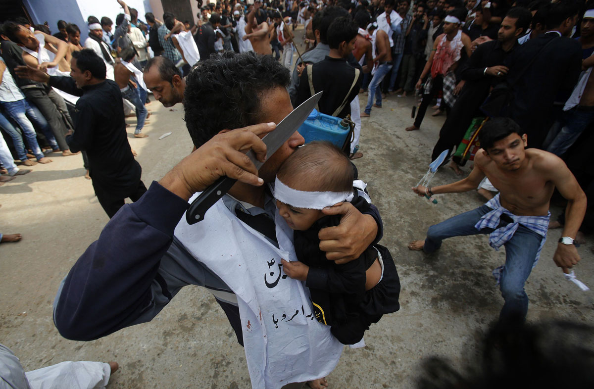 A Shi'ite Muslim man uses a knife to gash a child's head during a Muharram procession ahead of Ashura in Amroha