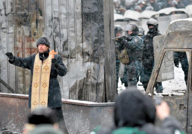 Placing himself in between factions, an Orthodox priest begs the people not to charge against shotgun armed police.