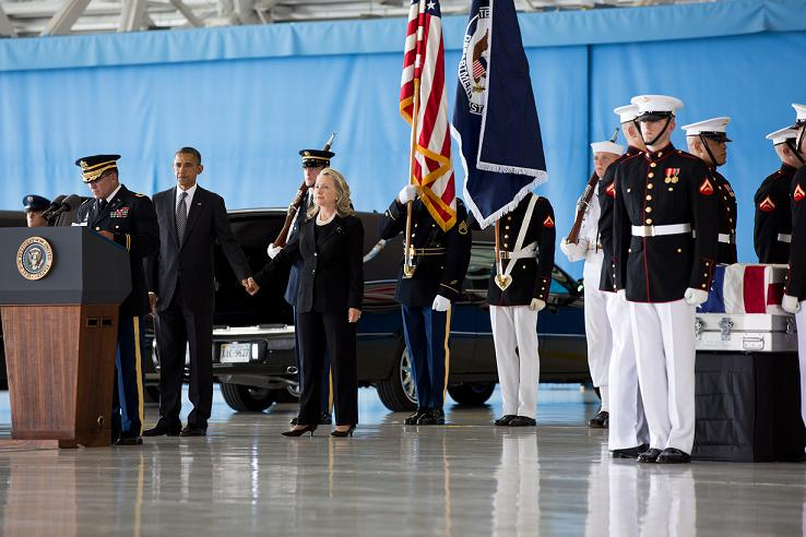 Obama and Clinton hold hands as Benghazi victims return home.