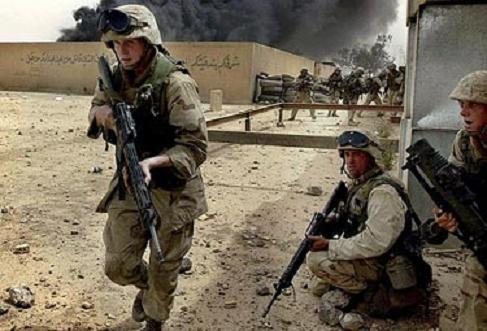 Lance Cpl. Stephen Ferris of Walpole, Mass., left, with India Co., 3rd Batt., 7th Marines, 1st Marine Division, advances on the headquarters of the Fedayeen in Baghdad on Wednesday, April 9, 2003. The Fedayeen are a secret fighting force controlled by Saddam Hussein. (AP Photo/Laura Rauch)
