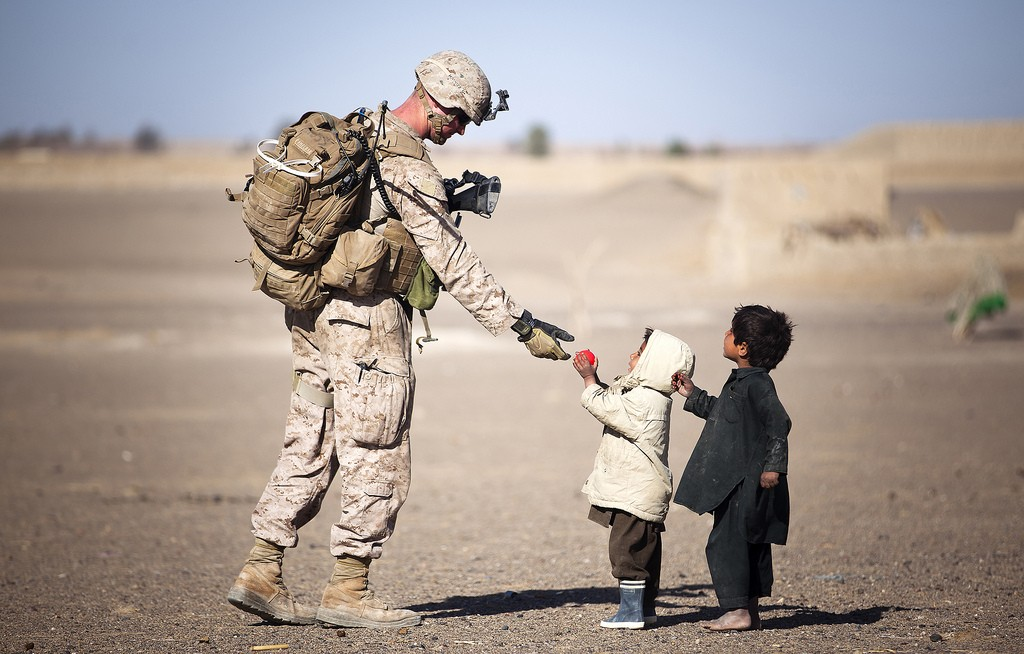 U.S. Marine Lance Cpl. Tom Morton, a 23-year-old team leader with 3rd Platoon, Kilo Company, 3rd Battalion, 3rd Marine Regiment, and native of Nashville, Tenn., hands an Afghan child a toy during a security patrol. (Photo: Flickr)