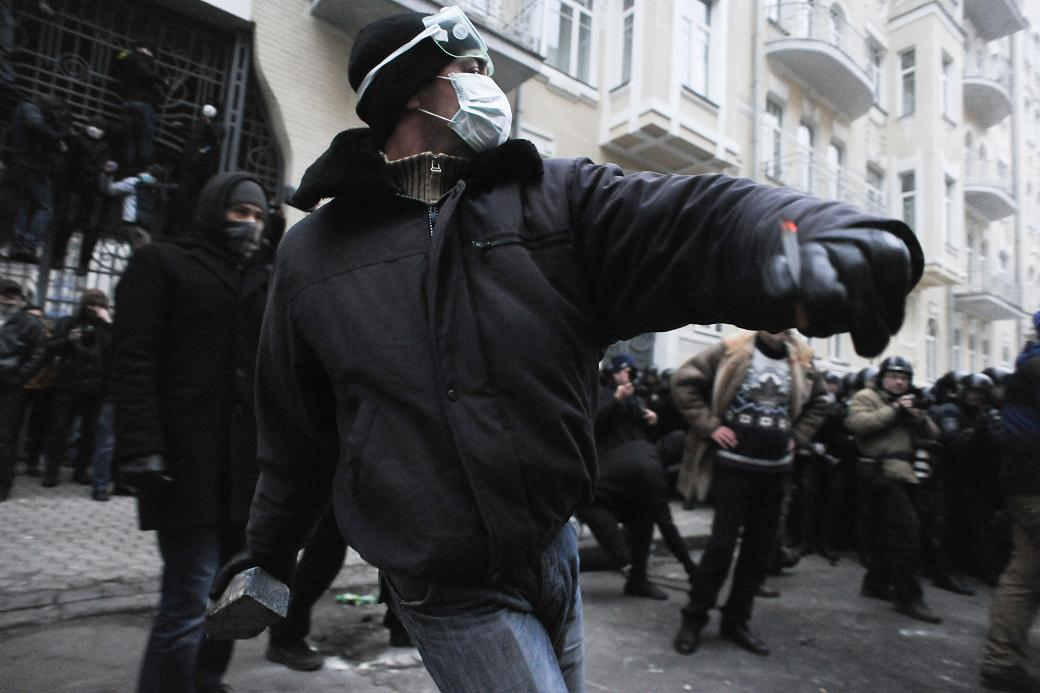All too familiar scene of a protester throwing a paving stone at police - Ukraine, 2013.